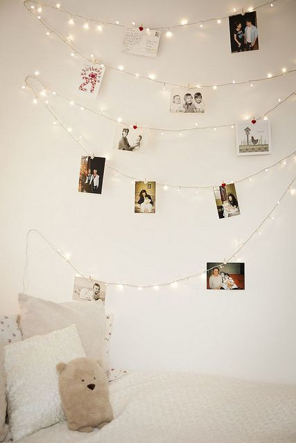 string lights with photos hanging on them over the bed