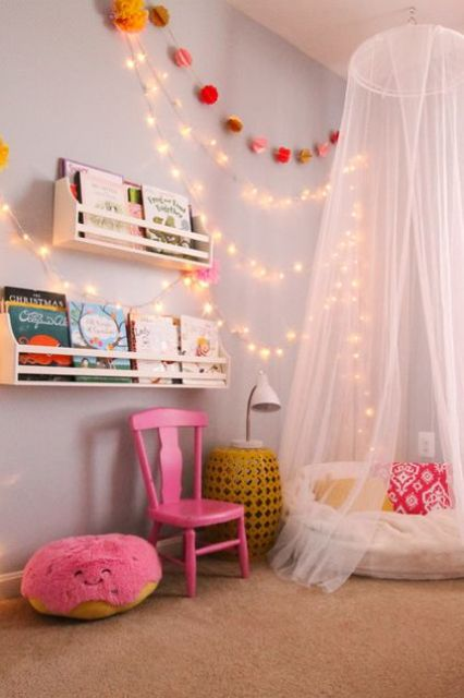 a colorful reading nook with a teepee and string lights on the wall
