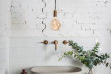 18 exposed white brick and white tiles plus white concrete make the bathroom bolder though it's monochrome