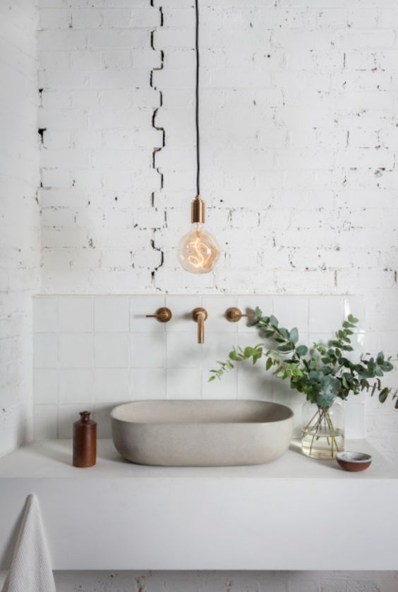 exposed white brick and white tiles plus white concrete make the bathroom bolder though it's monochrome
