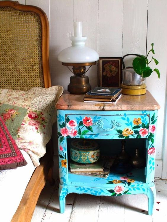 a blue vintage floral painted nightstand with a wooden top for a spring feel