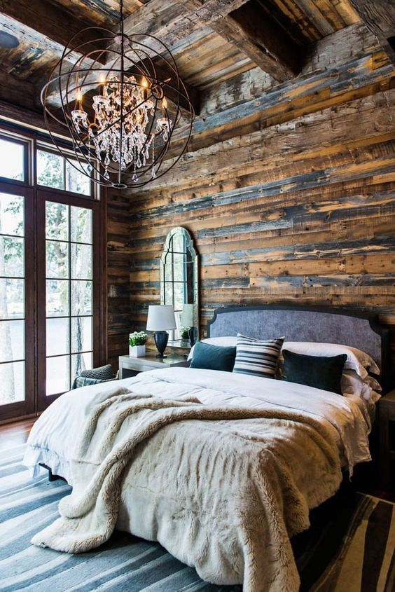 a rustic chalet bedroom done with an industrial chandelier with crystals that makes the space cooler