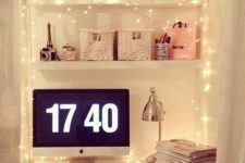 19 a small girlish workspace with string lights hanging on the shelves over it