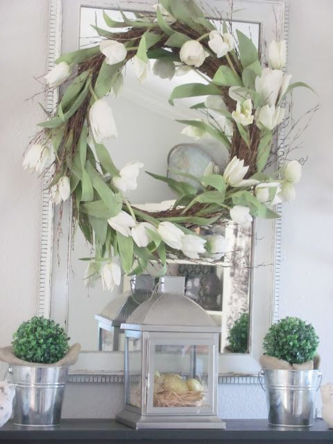 a wreath with white tulips, potted boxwood and a lantern with eggs in a nest