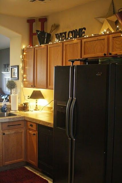 string lights going up the kitchen cabinets are a cute idea to try