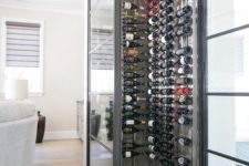 20 a chic small wine cellar highlighted with framed glass walls to keep a proper temperature inside