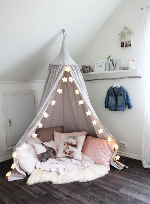 a cute tent for reading and playing with star-shaped string lights to add more light to the corner