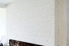 20 a whole fireplace wall clad with white brick with firewood storage and a hearth