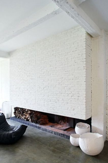 a whole fireplace wall clad with white brick with firewood storage and a hearth