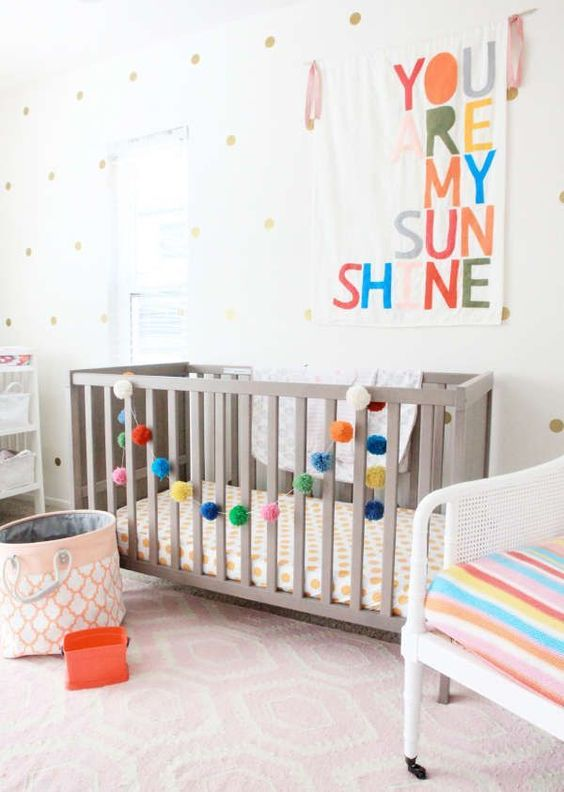 add touches of color to your gender neutral nursery with bright upholstery, a colorful pompom garland and a sign