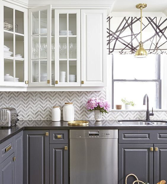 a bold kitchen with a grey and white chevron tile backsplash and a geo roman shade