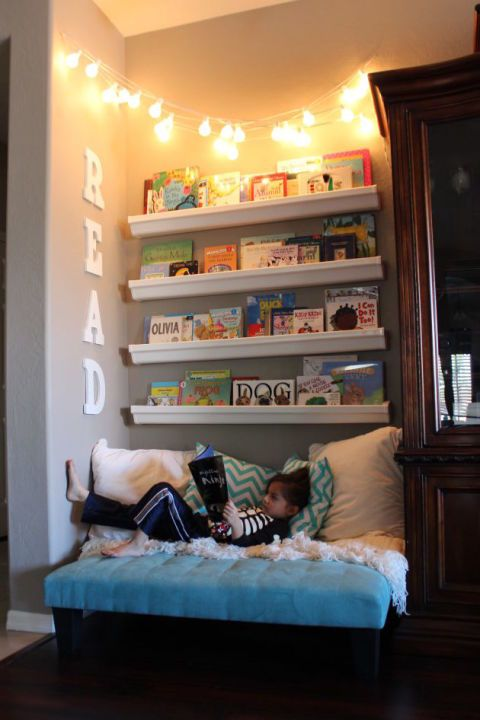 a reading nook with an upholstered bench and shelves plus string lights over it