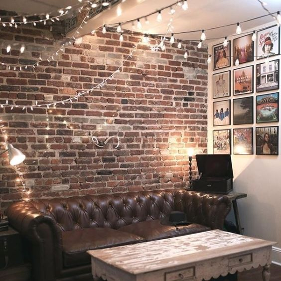 An Industrial Living Room With Lots Of String Lights All Over The Room