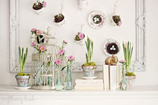 a bird cage with blooms, potted bulbs and an artwork with hanging cups with nests inside