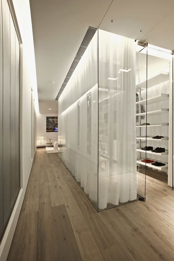 a stylish glass walled closet with lots of open shelves is made more private with curtains