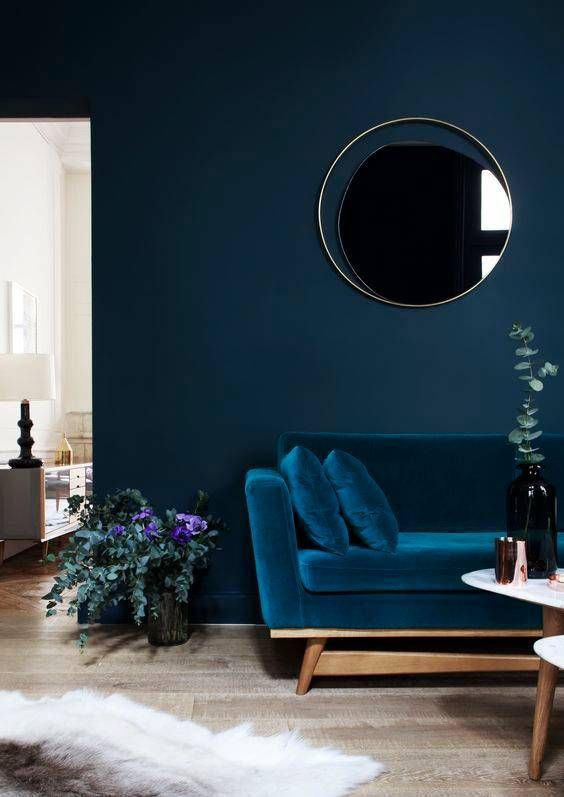 a very chic living room with a velvet sofa that matches the wall color