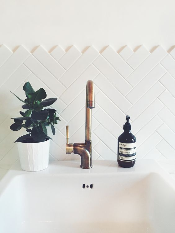 clad a bathroom backsplash with long and narrow tiles in a chevron pattern