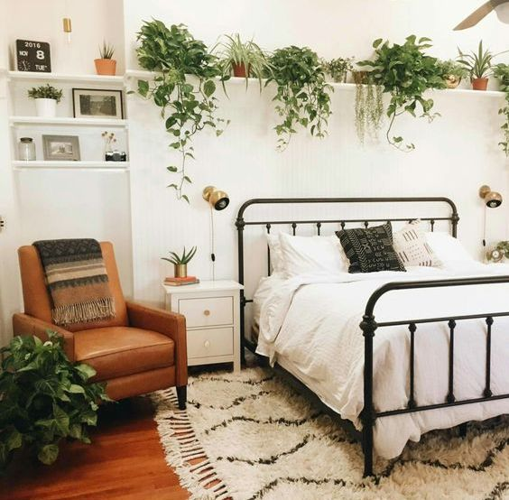 a ledge over the bed with lots of planters and pots with cascading greenery