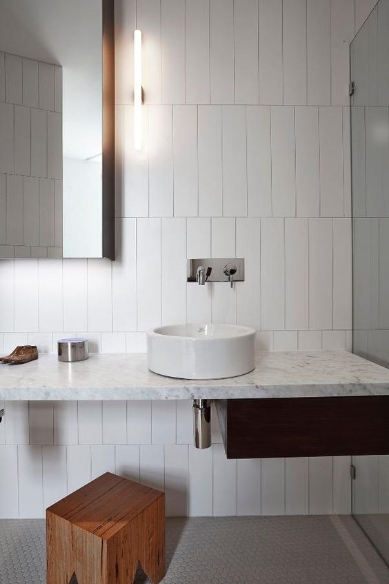 a minimalist bathroom is done with long and narrow white tiles accented with dark grout