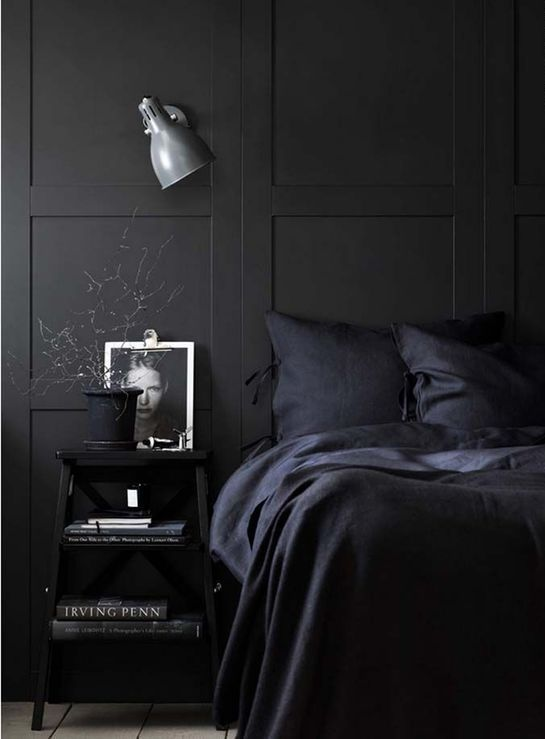 an all-black bedroom with a grey sconce as the only touch of a different color
