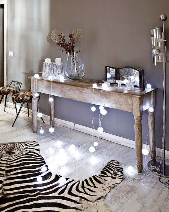 ball-shaped string lights on a vintage wooden console table for a more modern feel