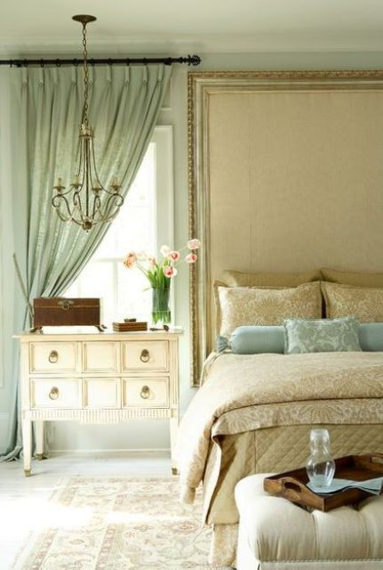 the neutral bedroom is spruced up with a mint colored curtain and matching pillows