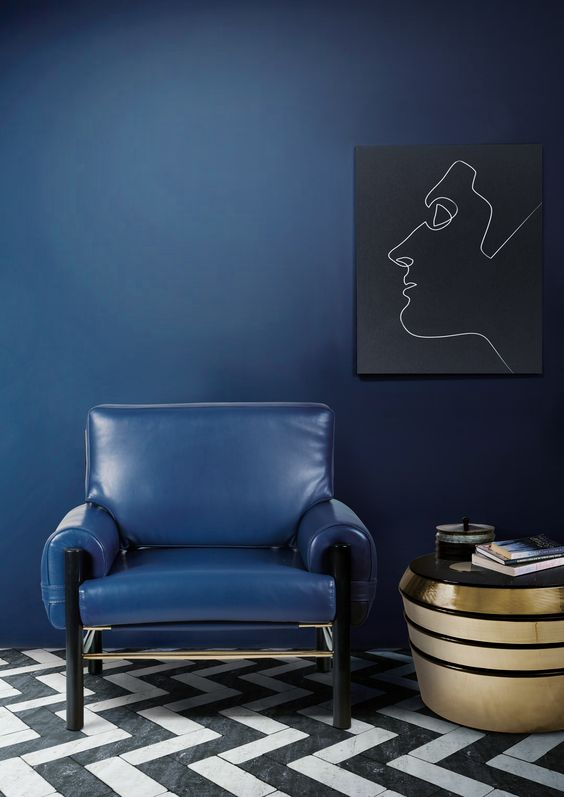 a navy wall and a matching leather chair plus a gold coffee table and an artwork create a very elegant look
