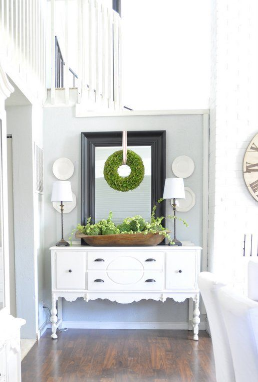 a wooden bowl with fresh greenery and moss balls and a greenery wreath on the mirror