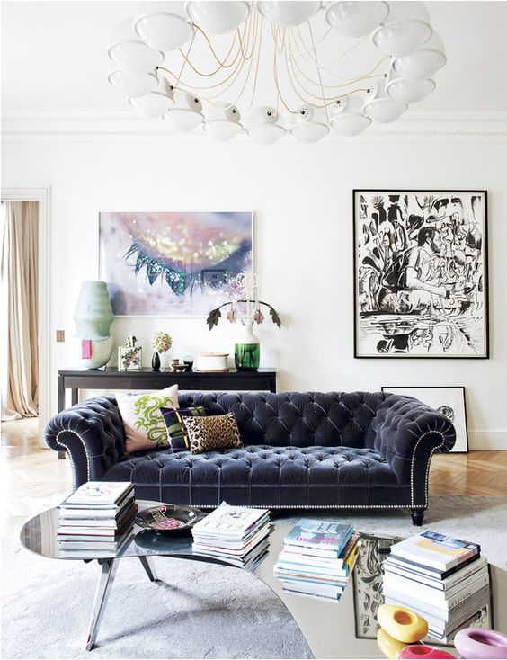 an airy living room in neutral shades with a bold velvet Chesterfield and artworks