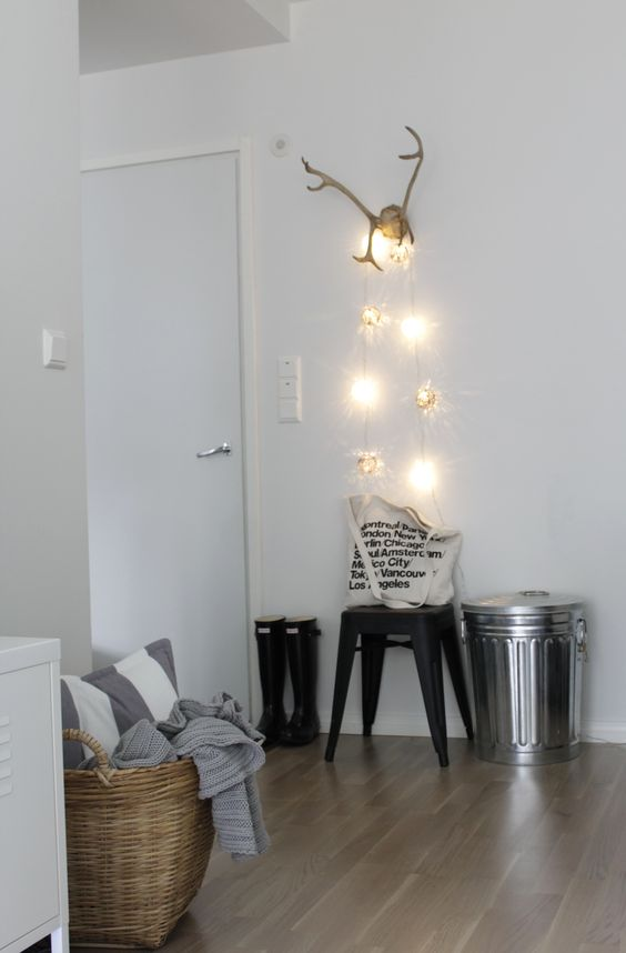 hang some creative lights on the antlers that you use as a coat and scarf hanger
