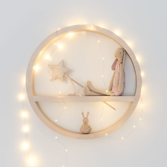 a circle toy shelf with string lights covering it for a highlight