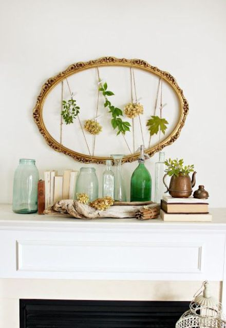an artwork of a vintage oval frame with fresh leaves and blooms and greenery in a pot plus green bottles