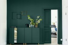 26 a dark green wall and a matching sideboard with brass legs to create a seamless look