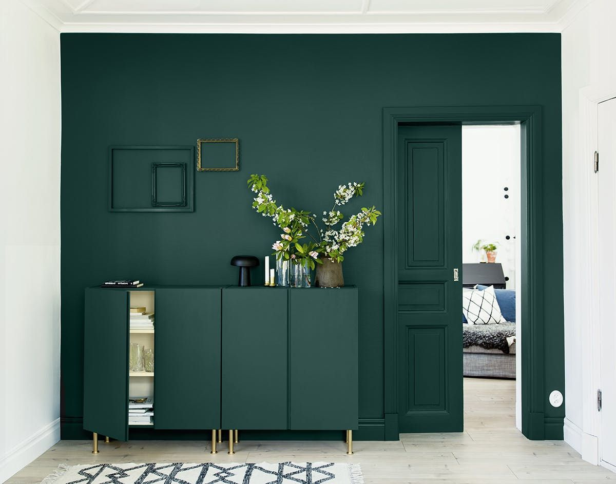 a dark green wall and a matching sideboard with brass legs to create a seamless look