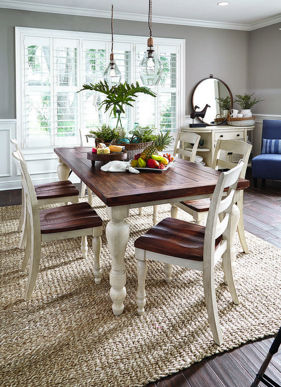 Country cottage-esque white and brown dining room table on a natural fiber rug.