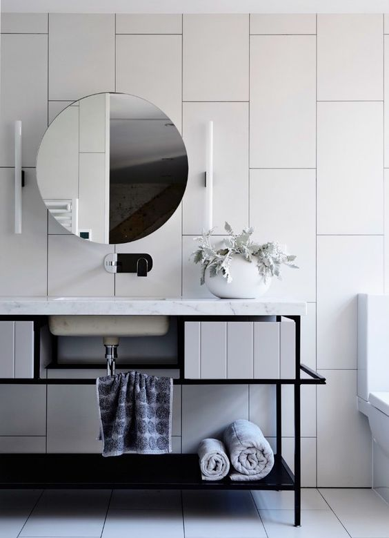 oversized white tiles create a wow effect in this bathroom and black grout helps to accent them