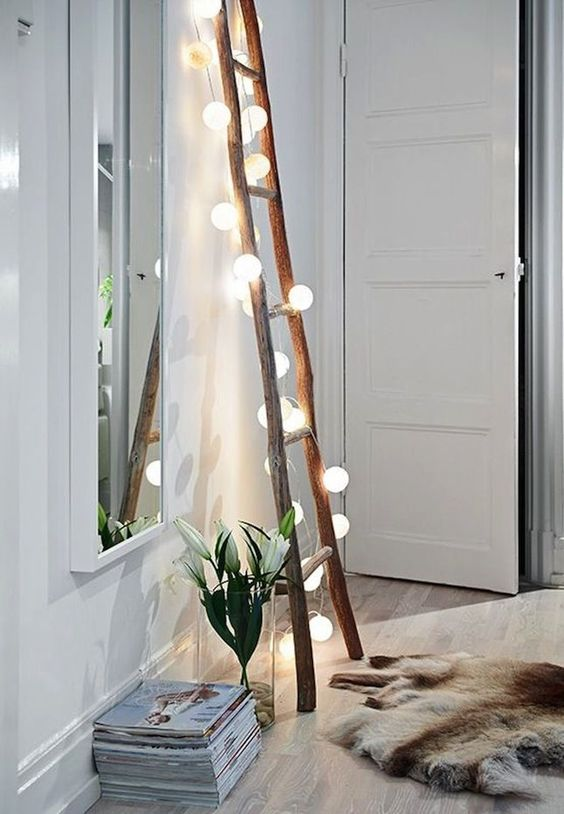 a ladder for storage covered with string lights