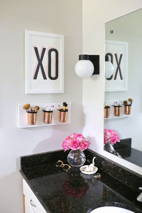 a small wall-mounted bathroom organizer with copper jars for makeup stuff