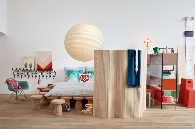 The bedroom is bold and bright, the bed is placed on cork stools, and there's much colorful furniture