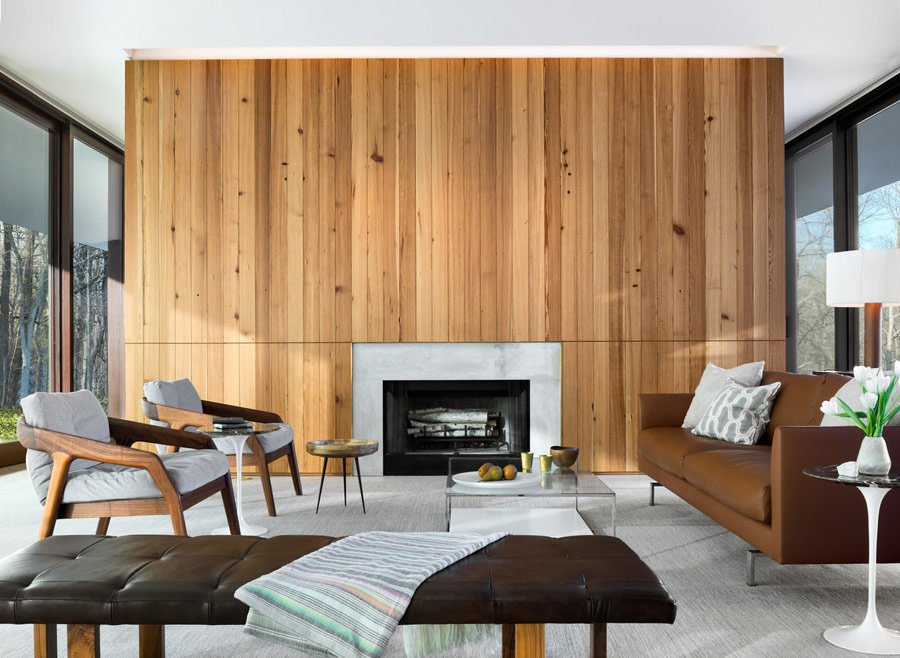 The living room of the house is done with a wood clad wall and a built in fireplace, there's chic mid century furniture and some contemporary touches, too