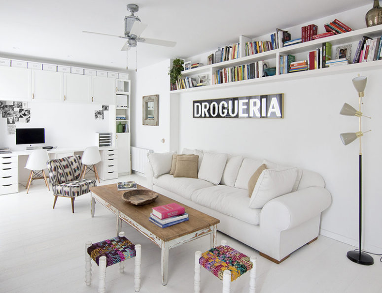 The living room with a home office nook is done with colorful and eclectic furniture