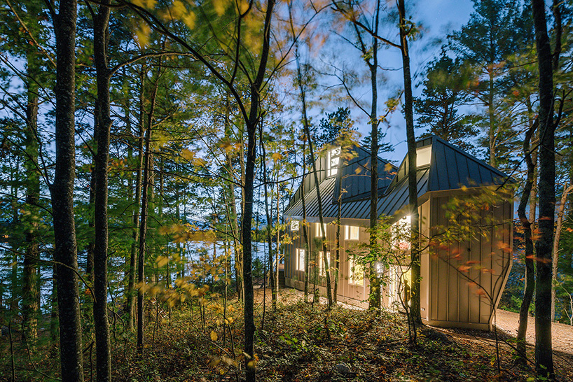 This lakeside house with creative architecture is situated inside a forest on a lake shore