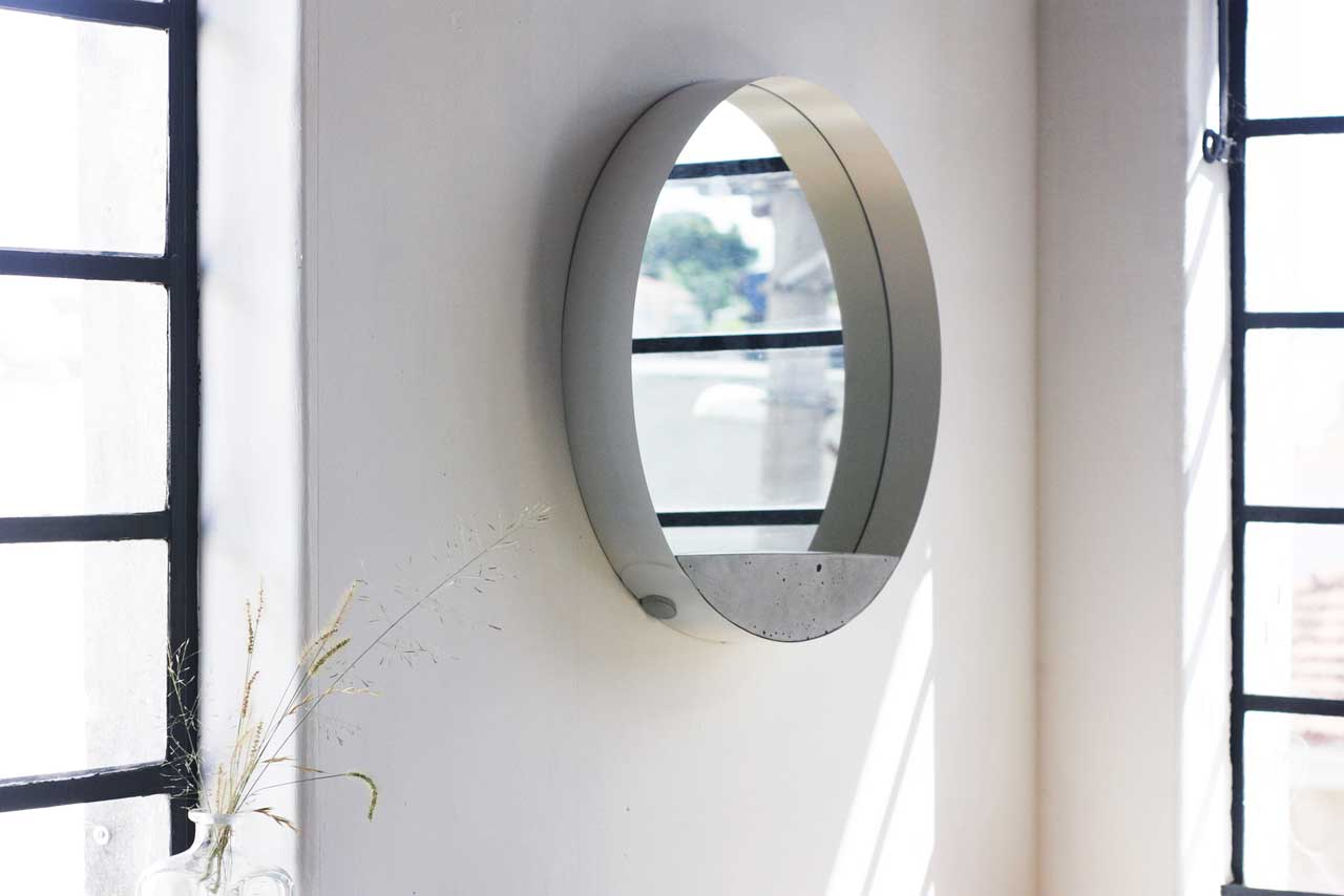 This sleek modern mirror is made of concrete, a metal loop and mirror for a modern or industrial space