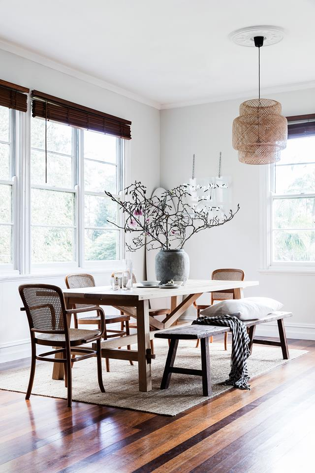 A formal dining space with wooden Roman shades, a woven lamp and comfy furniture is necessary for receiving guests