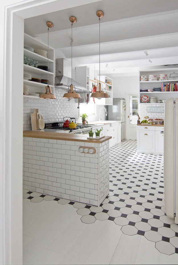 The kitchen features black and white floor and white subway tiles plus wooden touches