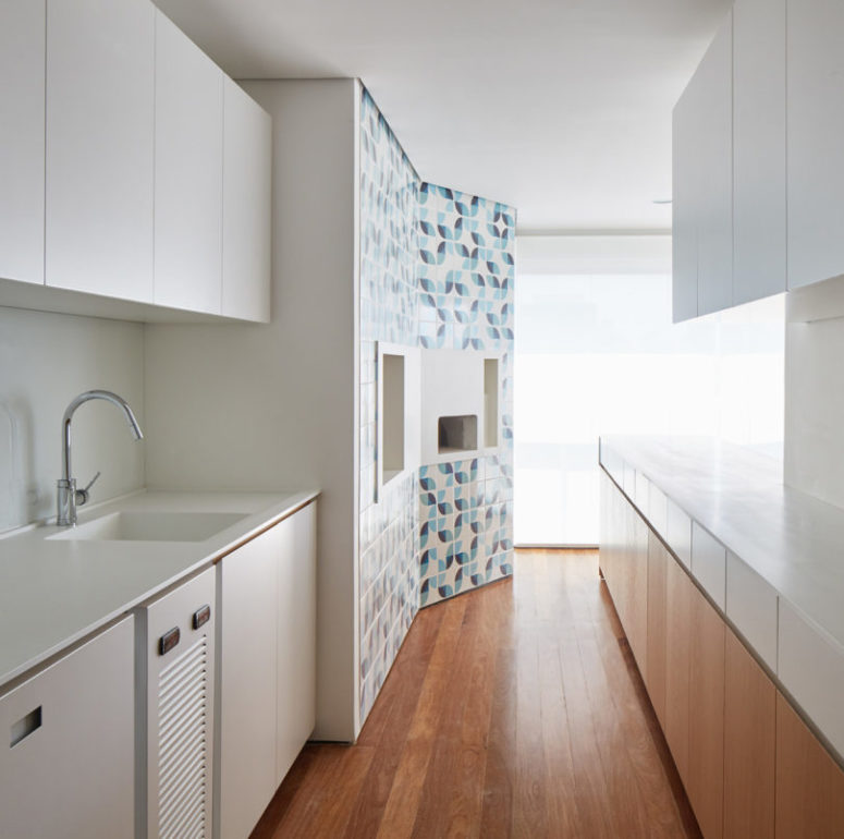 The kitchen is done with white and light-colored wooden cabinets and looks clean and sleek