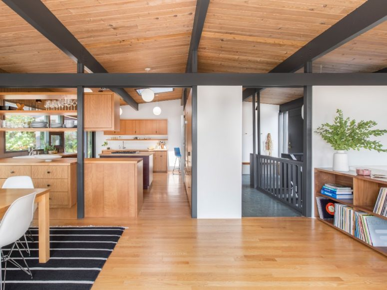 The main space is an open layout that comprises a kitchen, a dining room and a living space, it's clad with light-colored wood and there are dark exposed beams