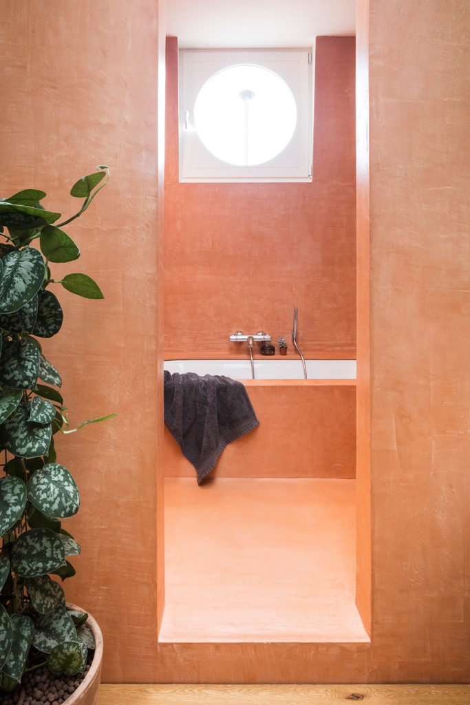 The spaces are done with raw materials for a texture, this bathroom is done in orange for a cheerful feel