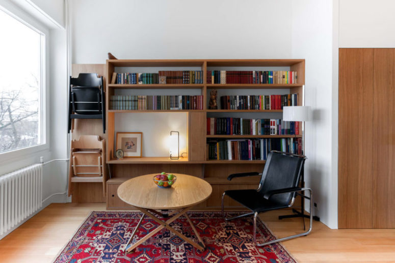 This is a small living reading nook with a large bookshelf and a sitting space plus a view