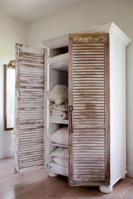a gorgeous wardrobe with doors changed for old shutters adds texture and sophistication to the space